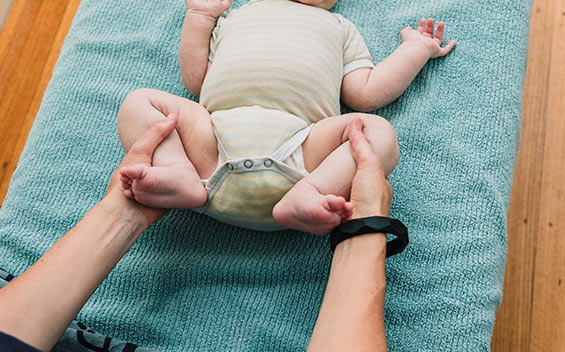Osteopath assessing baby with gentle leg movement