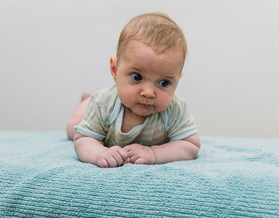 Baby smiling crawling on an osteopath table in Melbourne osteo clinic