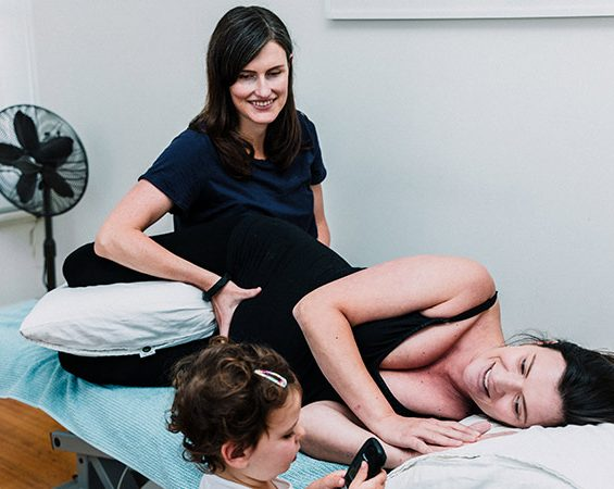 Female Osteopath with hand on pregnant women's stomach and toddler next to mum