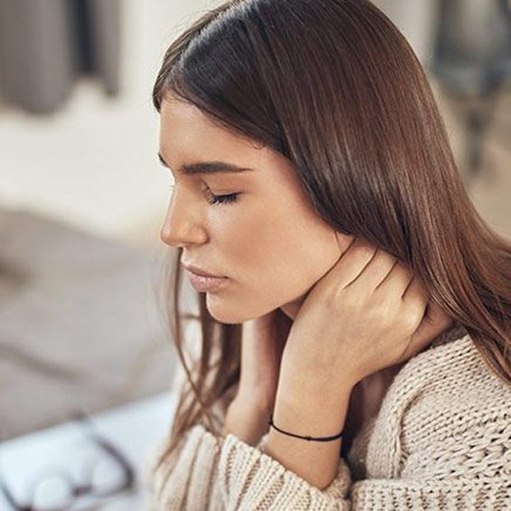 woman with neck pain holding her neck