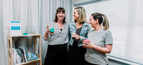 3 osteopaths smiling with coffee in Growing Bones Melbourne clinic