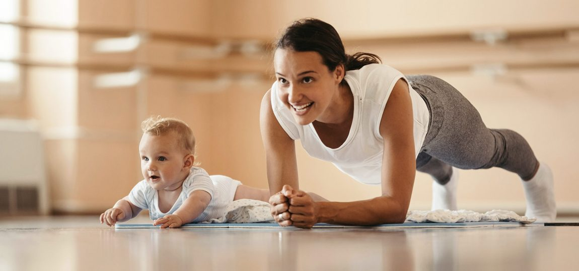 Healthy woman doing a plank with her baby next to her after seeing osteopath