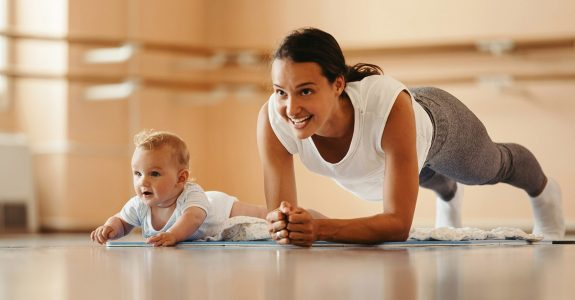 Healthy woman doing a plank with her baby next to her